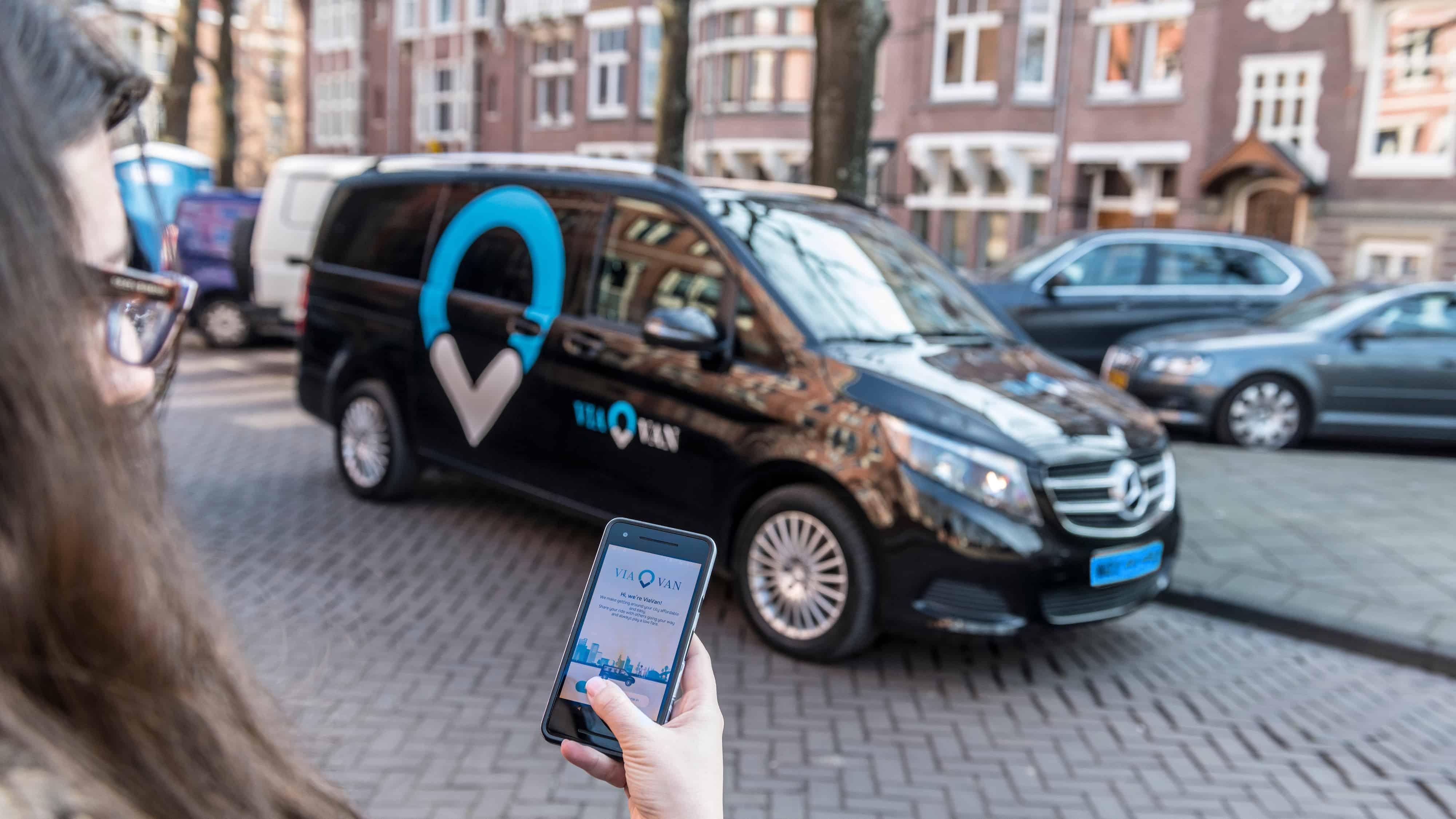Vrouw boekt een taxi via haar smartphone met de ViaVan app